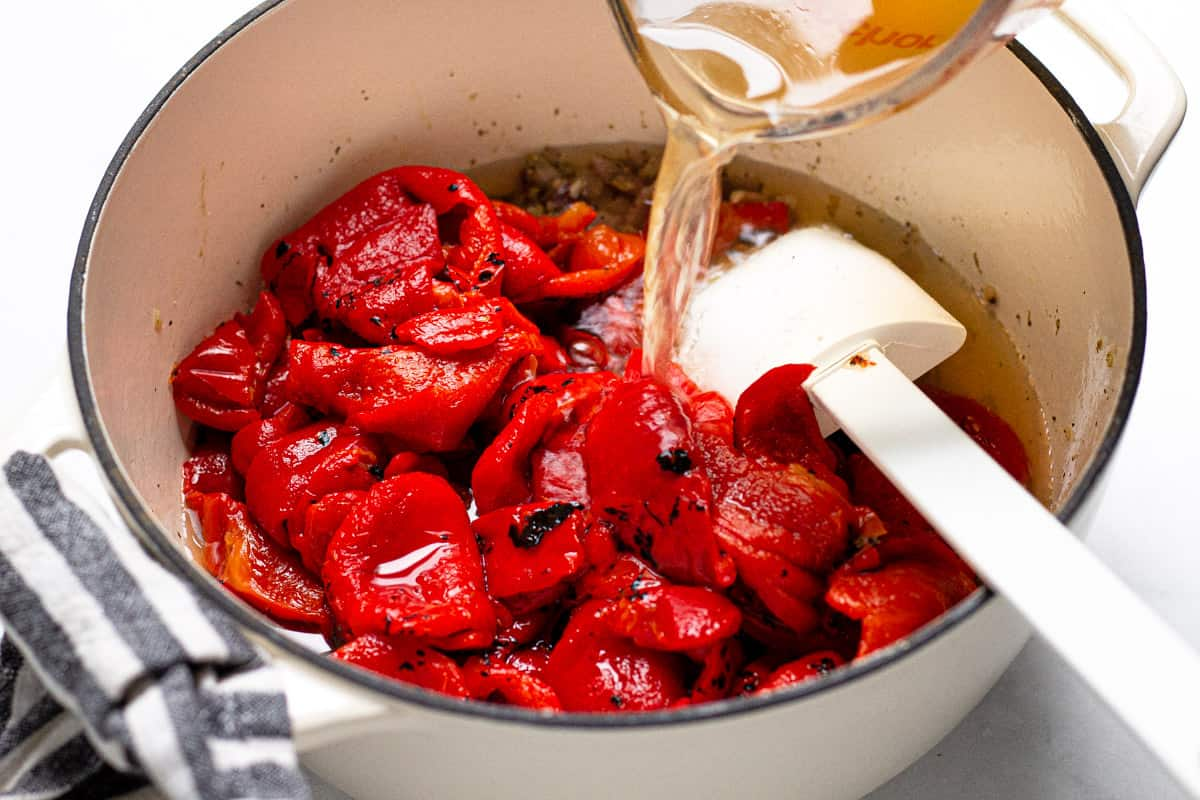 Large soup pot with ingredients to make roasted red pepper soup