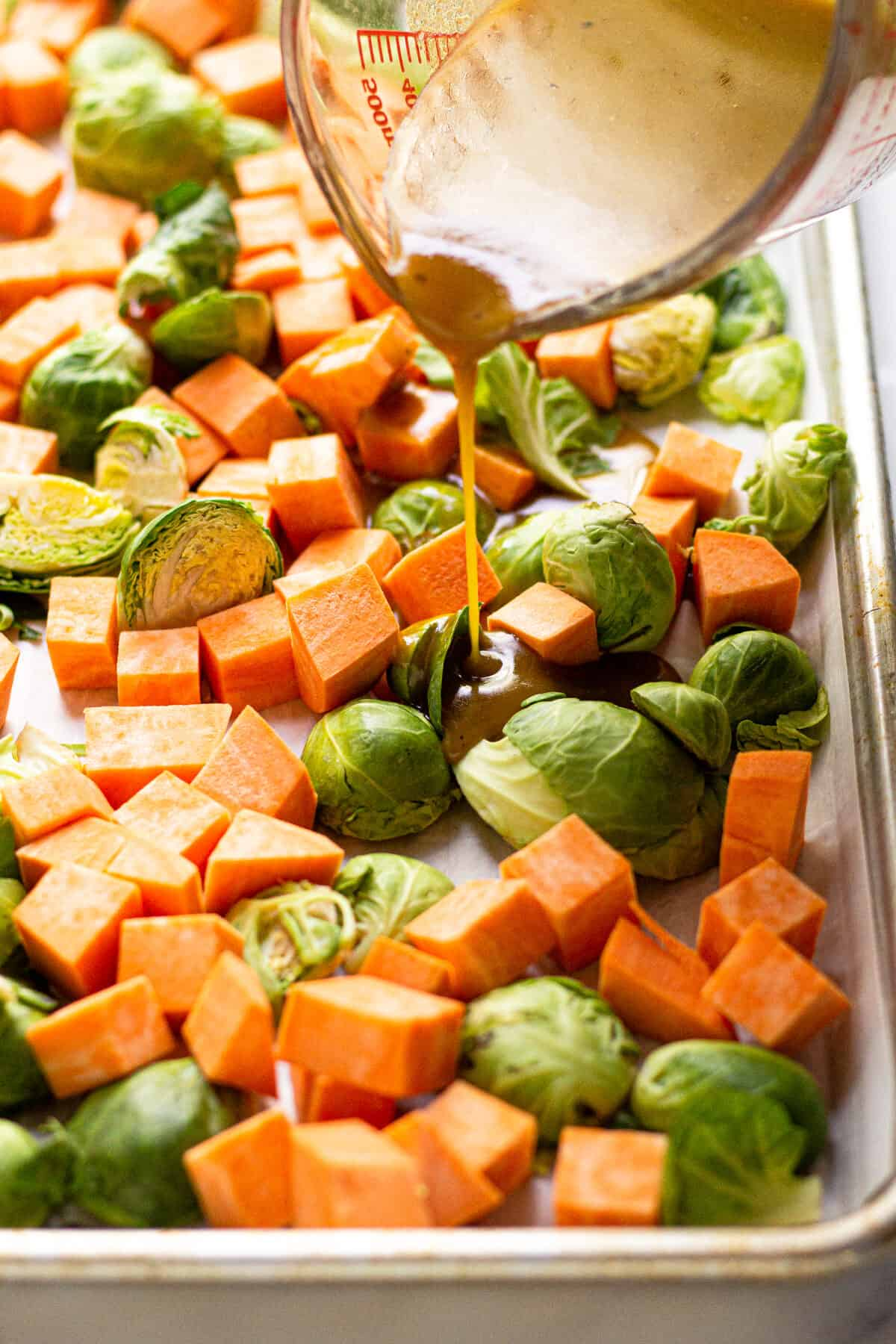 Maple mustard dressing being poured over a pan of Brussels sprouts and cubed sweet potatoes