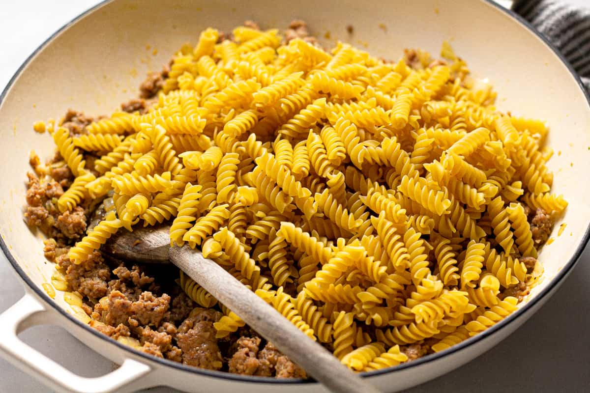 Large white pan with uncooked noodles and browned sausage