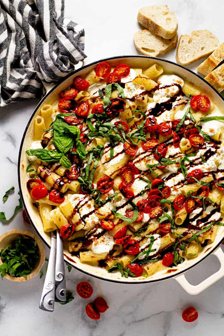 A pot of caprese mac and cheese garnished with fresh basil and balsamic glaze