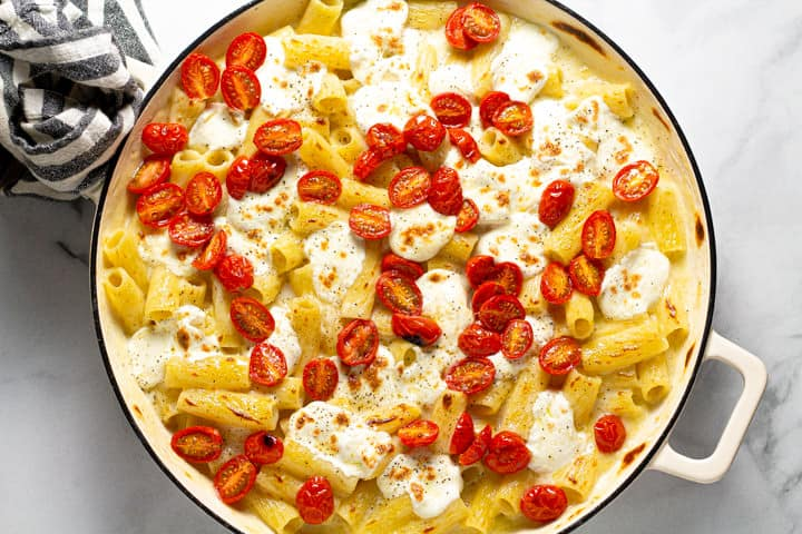 Rigatoni pasta in a creamy cheese sauce in a large white pot topped with fresh mozzarella and tomatoes