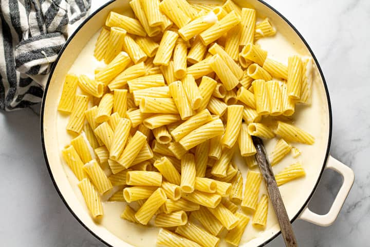 Rigatoni in a large pot of cheese sauce