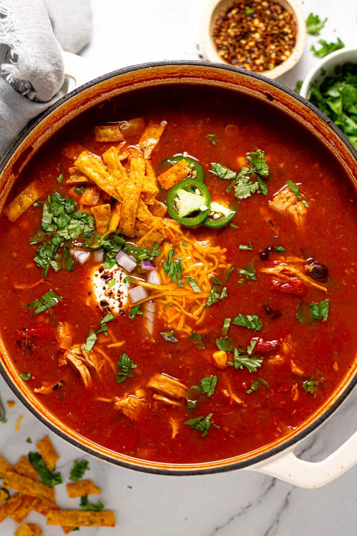 Overhead shot of a pot of chicken tortilla soup garnished with sour cream and shredded cheese