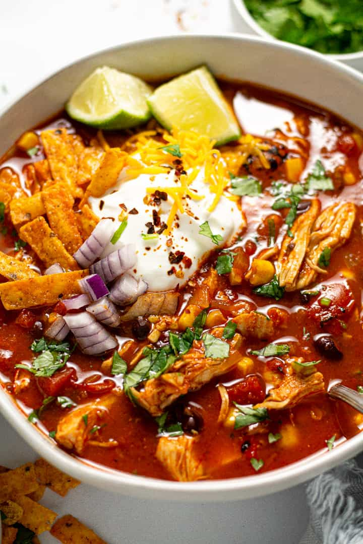 Close up shot of a bowl of chicken tortilla soup garnished with sour cream and shredded cheese