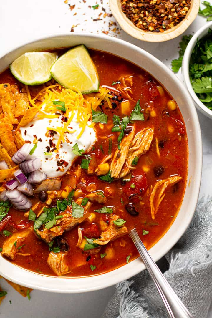 Overhead shot of a bowl of chicken tortilla soup garnished with sour cream and shredded cheese