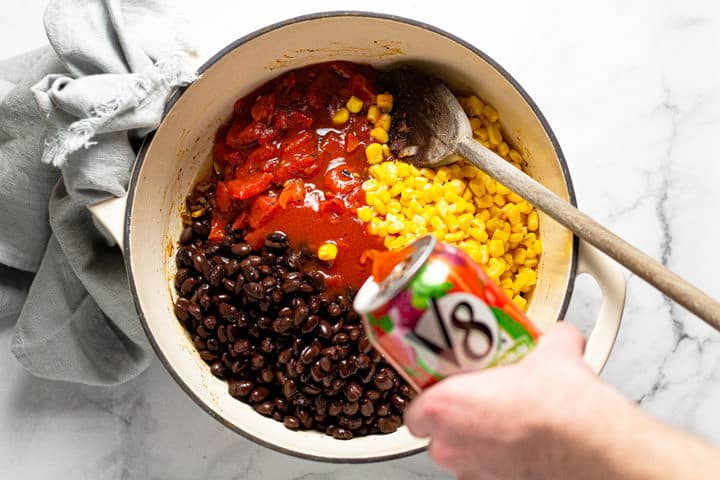 Large white pot with black beans corn and tomatoes with V8 being poured into it