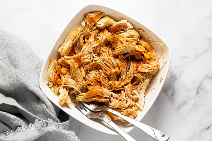 White bowl filled with shredded chicken and two forks