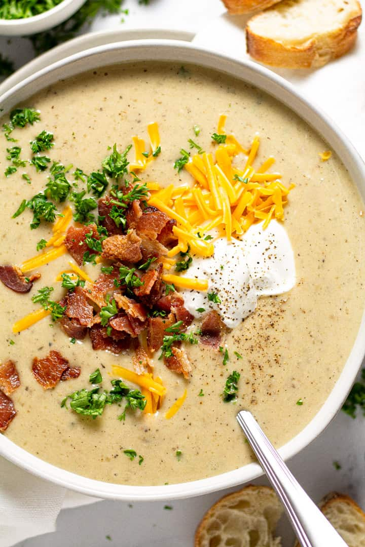 Overhead shot of a bowl of creamy potato soup garnished with cheddar cheese and bacon