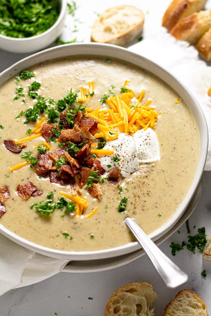 Close up shot of a bowl of creamy potato soup garnished with cheddar cheese and bacon