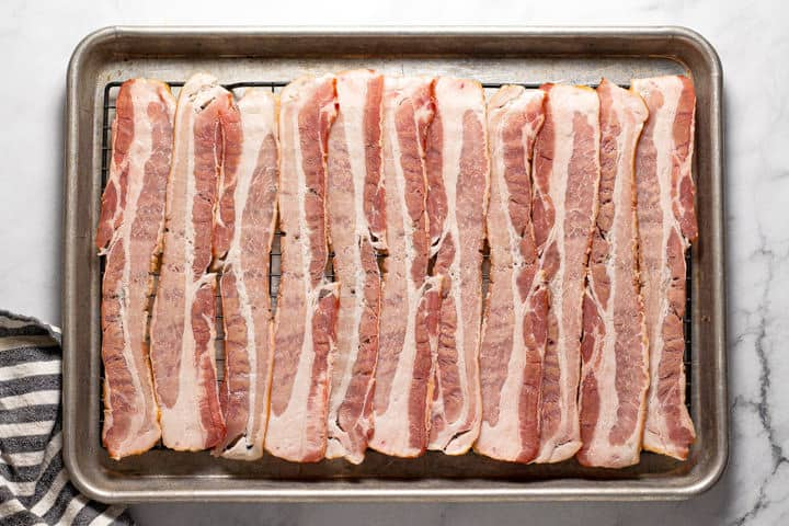 Baking sheet with raw bacon ready to be baking in the oven
