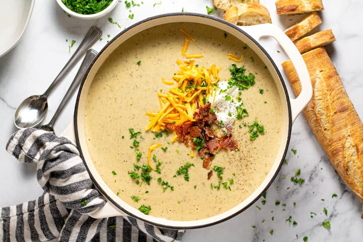 Overhead shot of a large pot of creamy potato soup garnished with cheddar cheese and bacon