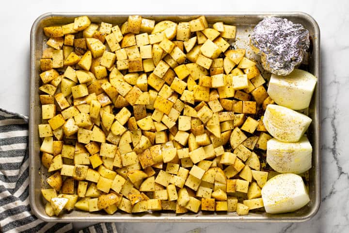 A sheet pan with diced potatoes onions and garlic seasoned with dried herbs