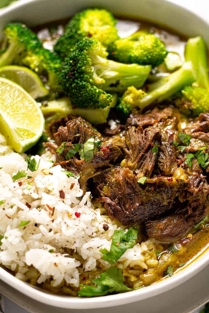 Close up shot of a bowl of curried beef served over rice and garnished with cilantro