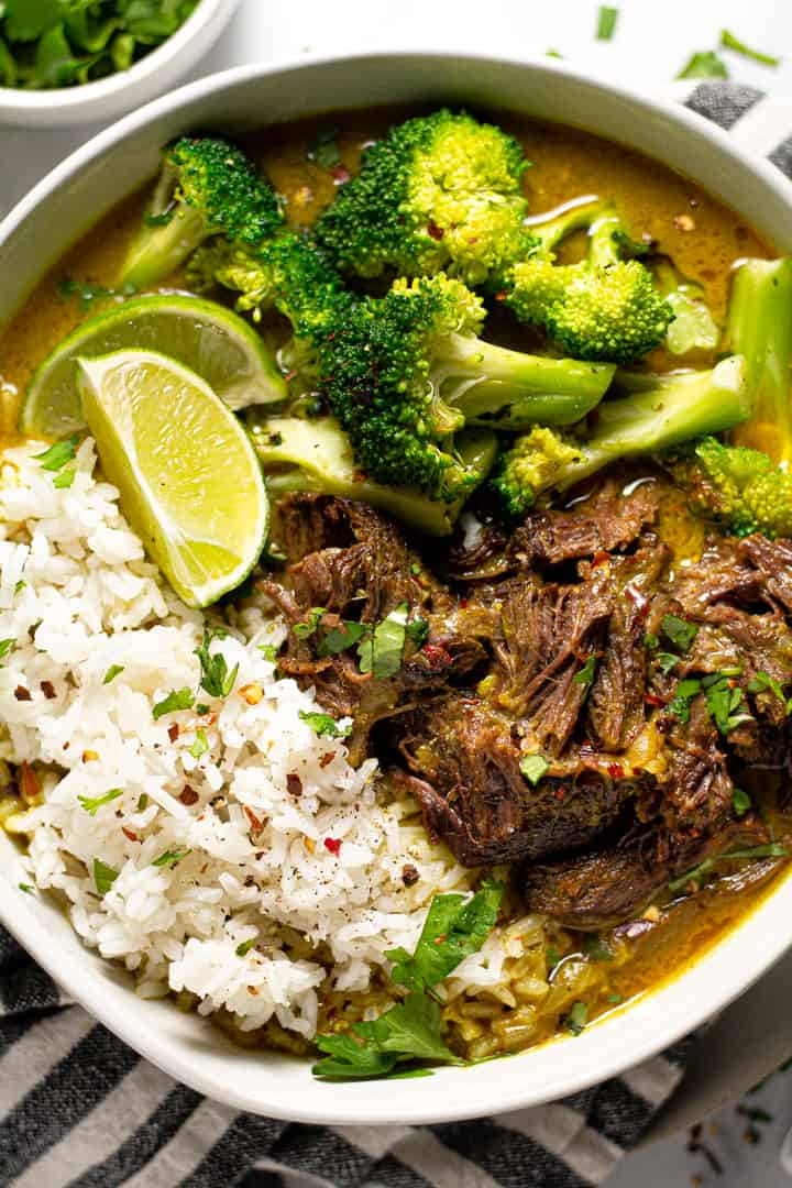 Overhead shot of a bowl of curried beef served over rice and garnished with cilantro