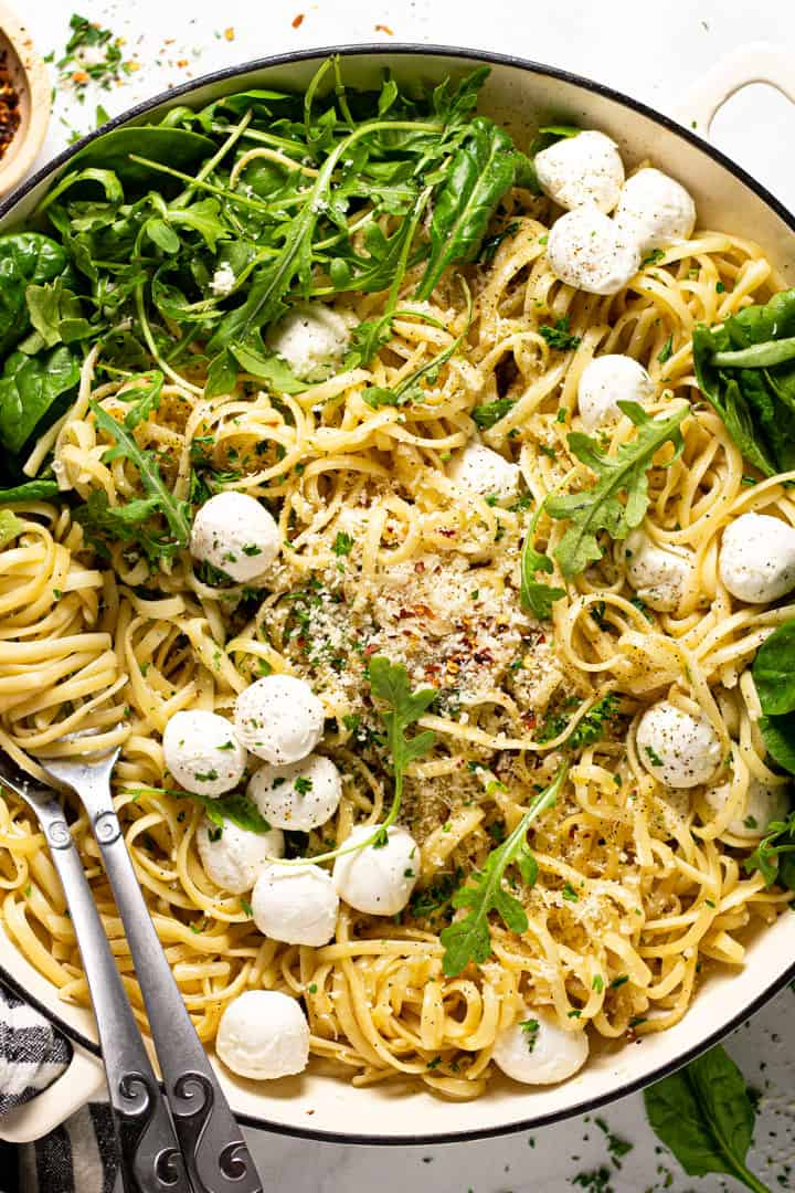 Overhead shot of a pan of garlic butter noodles garnished with Parmesan arugula and fresh mozzarella