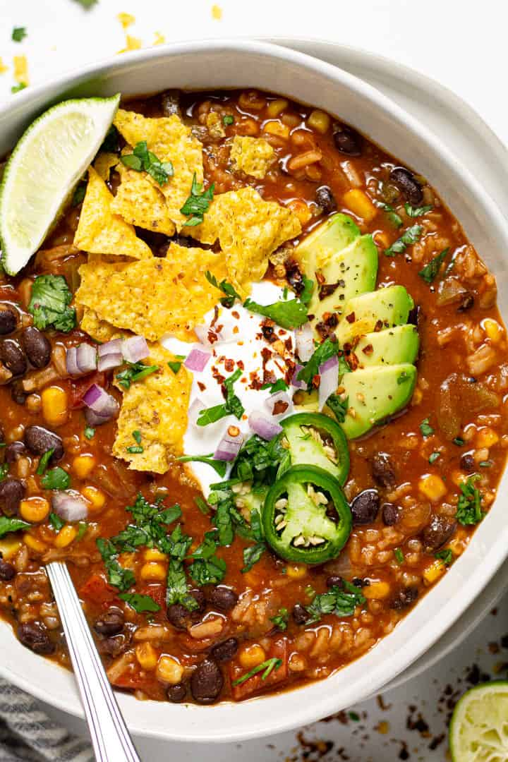 Overhead shot of a bowl of spicy black bean soup garnished with tortilla chips and sour cream