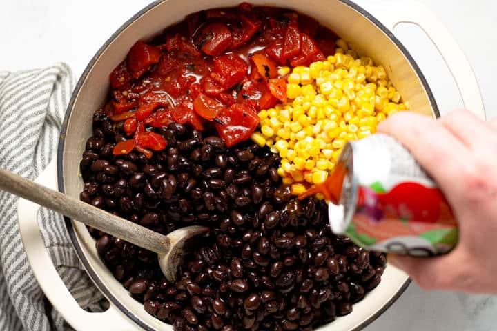 Large white pot filled with veggies and beans for black bean soup