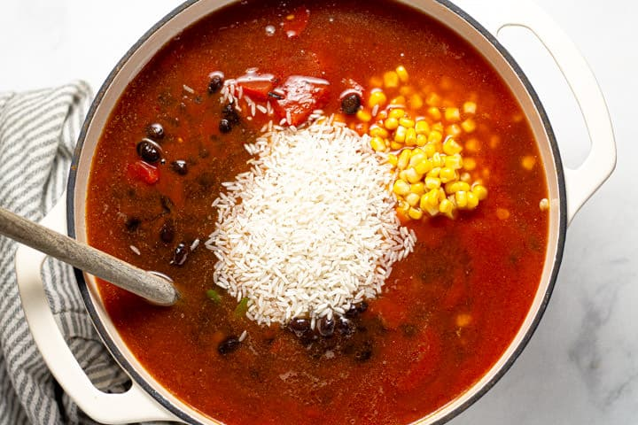 Large white pot filled with veggies  beans and rice for black bean soup