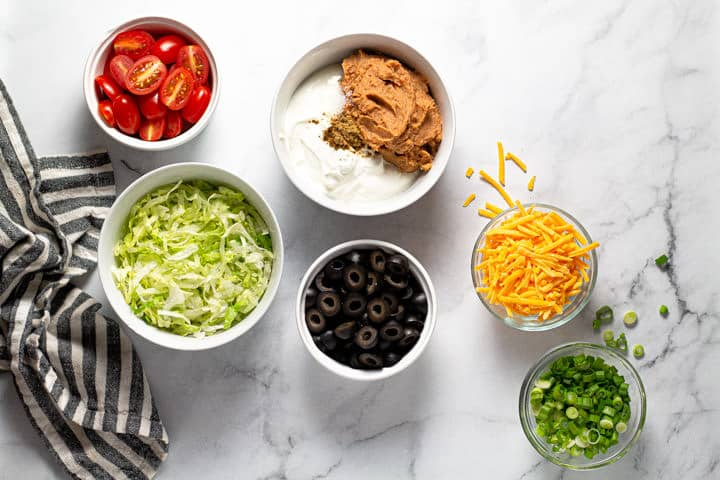 White marble counter top with ingredients to make taco dip