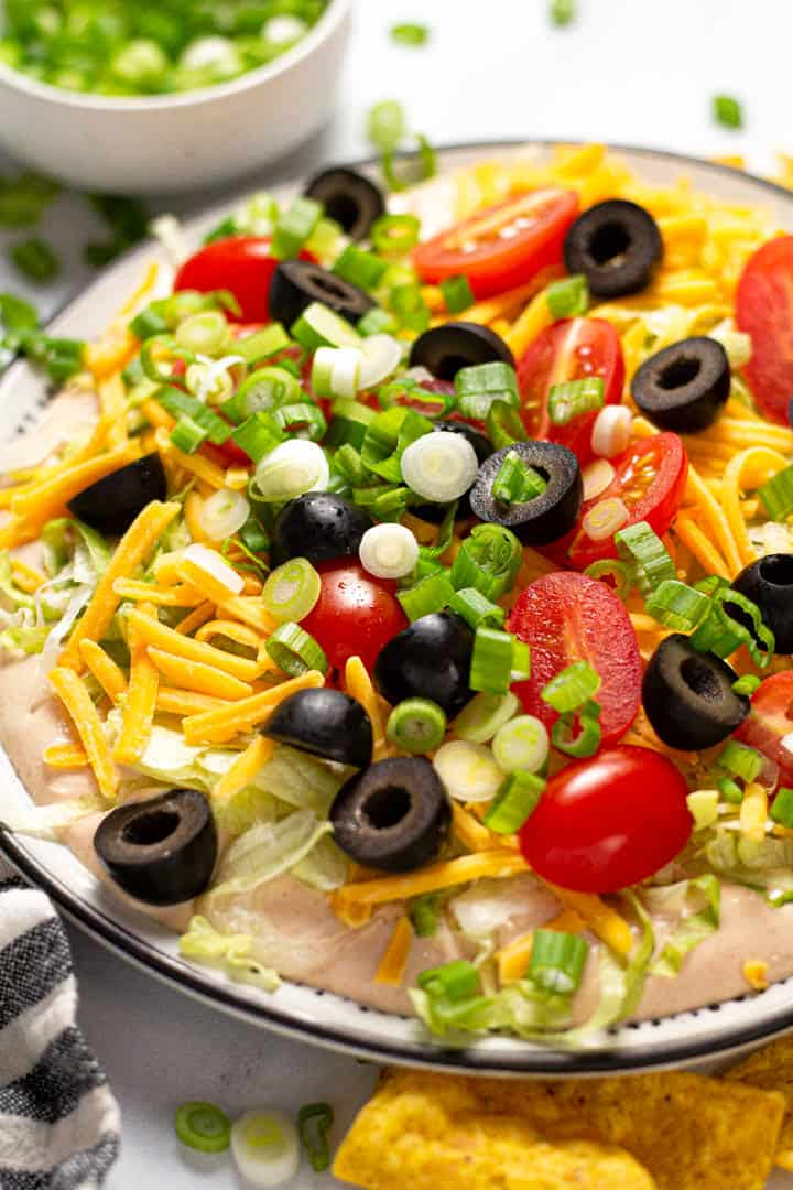 Close up shot of taco dip on a black and white plate served with tortilla chips