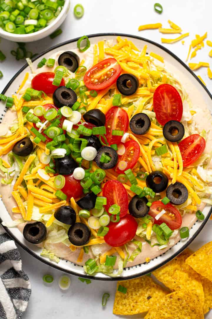 Overhead shot of taco dip on a black and white plate served with tortilla chips