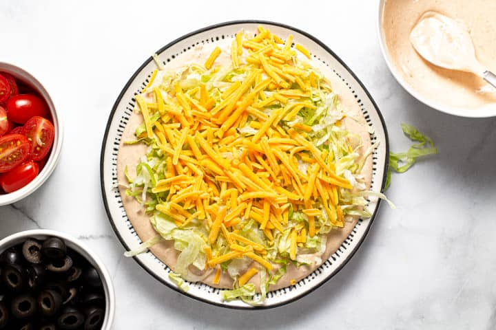 Taco dip being assembled on a black and white serving platter