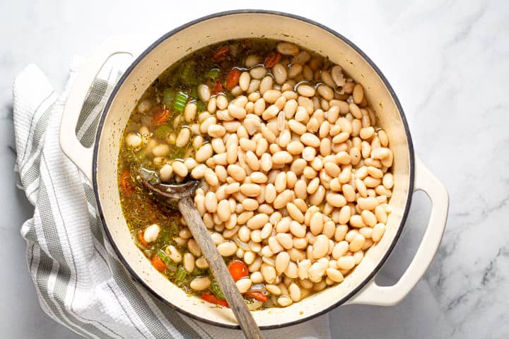 White beans veggies and broth in a large white pot with a wooden spoon