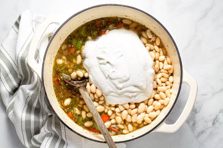 Coconut milk white beans veggies and broth in a large white pot