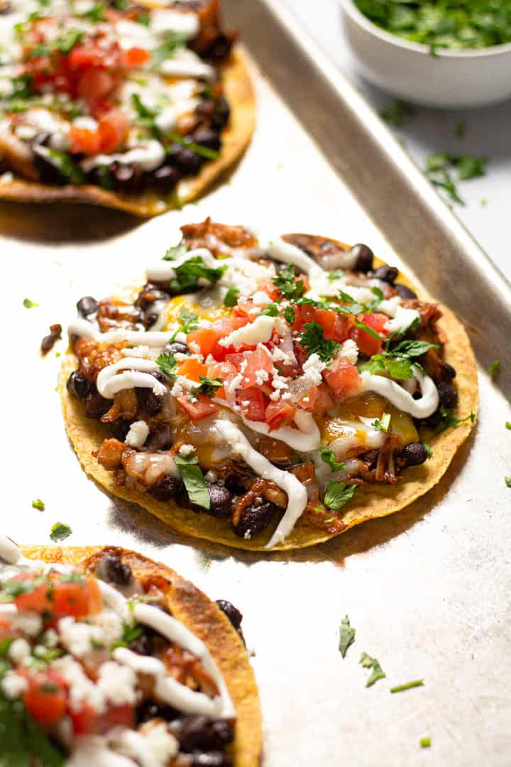Close up shot of a bbq chicken tostada on a large baking sheet