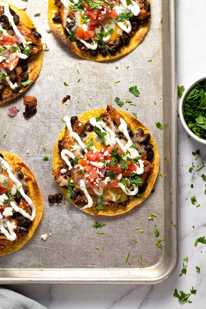 Overhead shot of a corner of a baking sheet with bbq chicken tostadas on it