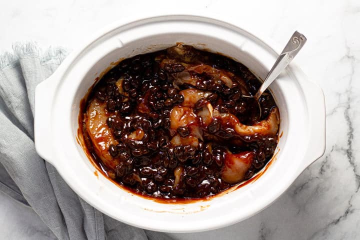 Overhead shot of a white slow cooker with BBQ chicken and beans in it