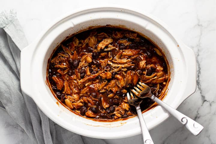 Overhead shot of a white slow cooker with shredded BBQ chicken and beans in it