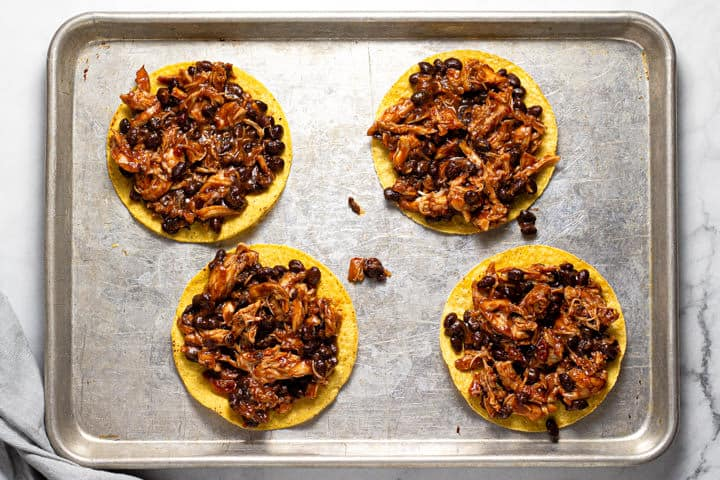 Shredded chicken and beans on top of 4 tostada shells on a baking sheet