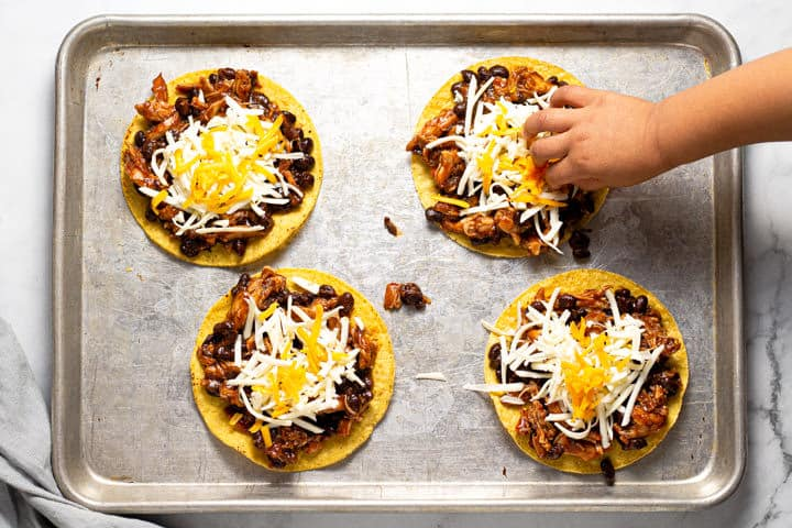A hand adding cheese to the top of a bbq chicken tostada on a baking sheet