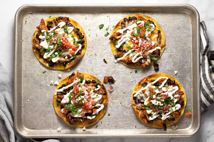 Overhead shot of a baking sheet with bbq chicken tostadas on it