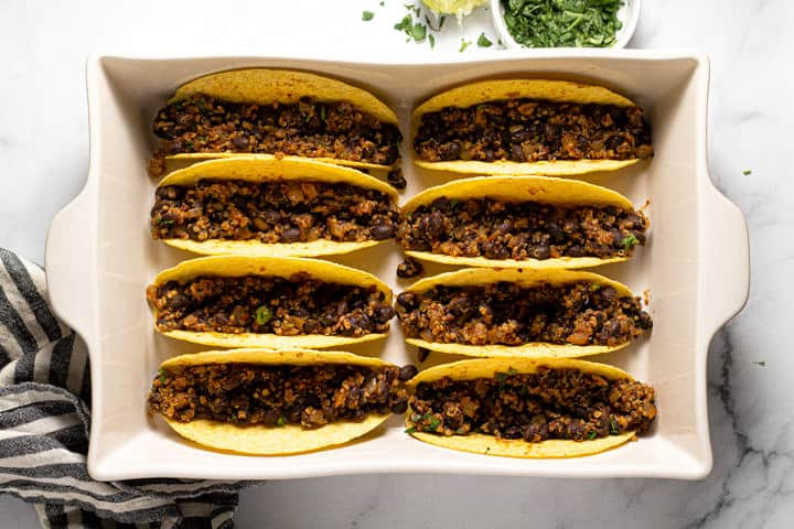 Overhead shot of a 9x13 baking dish filled with taco shells filled with vegan taco meat