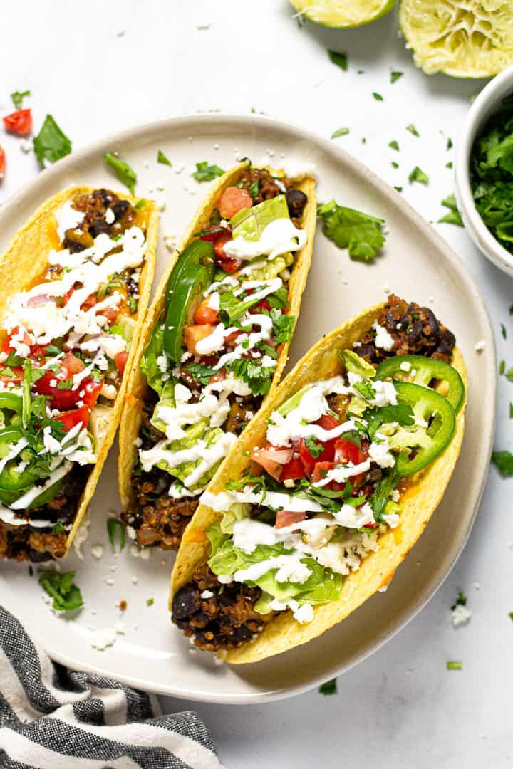Overhead shot of a white plate filled with baked black tacos garnished with fresh cilantro