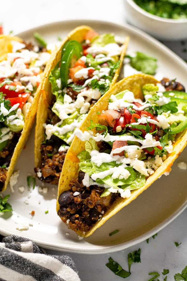 Close up shot of a white plate filled with baked black tacos garnished with fresh cilantro