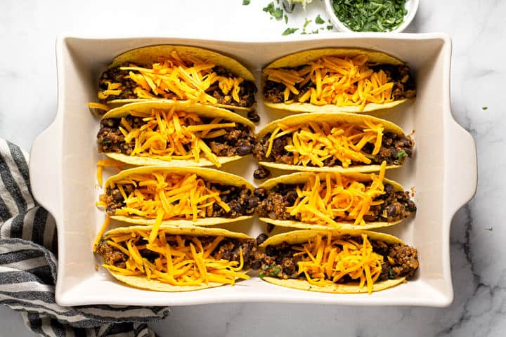 Overhead shot of a 9x13 baking dish filled with taco shells filled with vegan taco meat and cheese