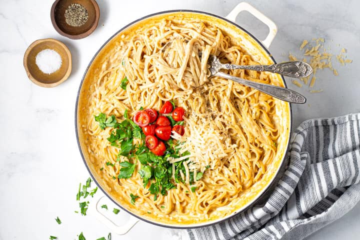 A large pot filled with fettuccine alfredo garnished with fresh parsley