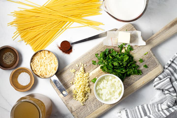White marble counter top with ingredients used to make fettuccine alfredo in one pot