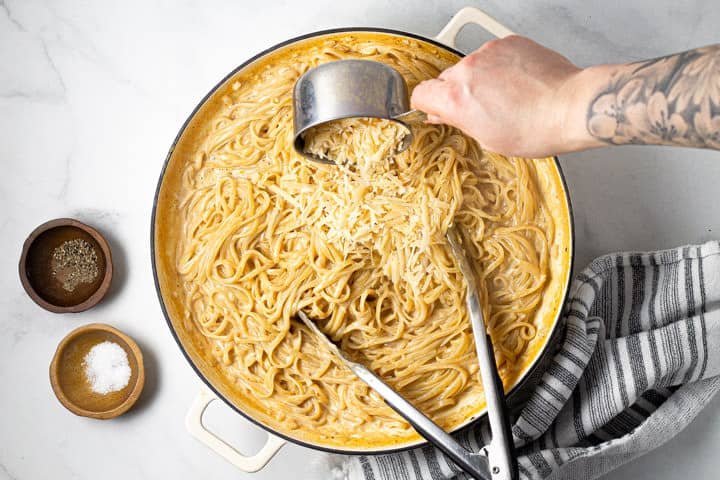 Large white pot filled with alfredo with a hand pouring Parmesan cheese over the pasta