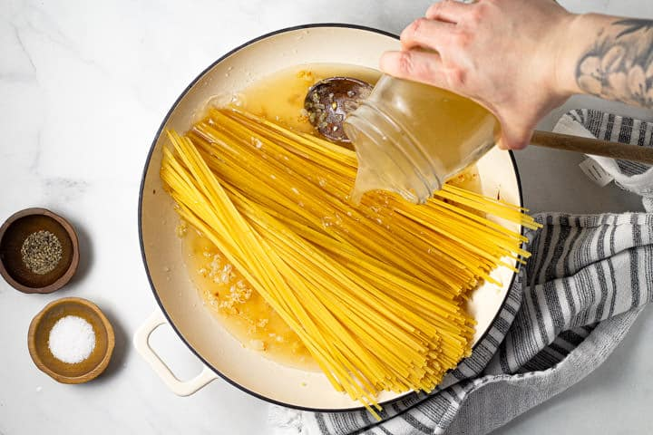 Large white pot with linguine noodles and a hand pouring broth over the noodles