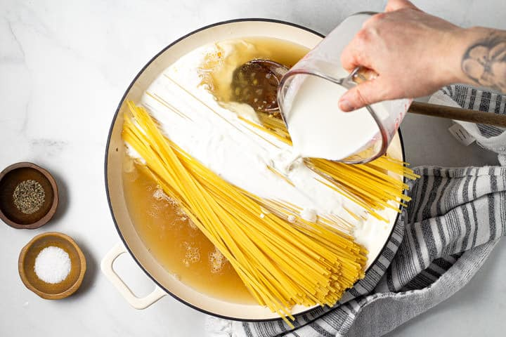 A hand pouring half and half over a pot of noodles