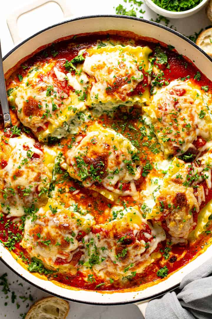 Overhead shot of a pan of spinach lasagna roll ups garnished with fresh parsley