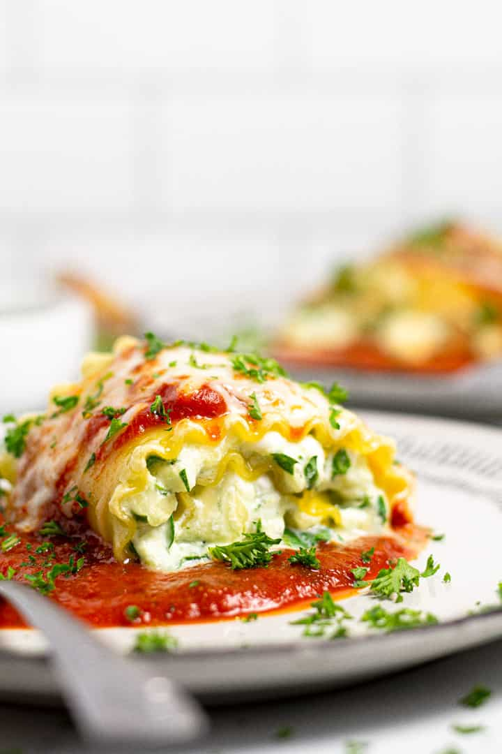 Close up shot of a spinach lasagna roll up garnished with fresh parsley