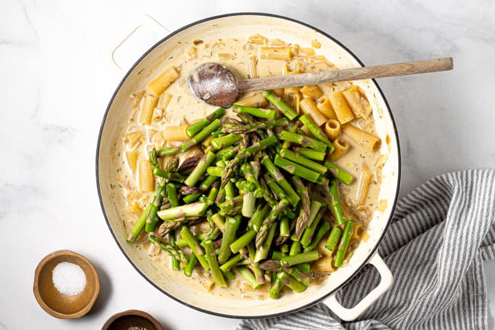 Chopped asparagus on top of cooked rigatoni in a large white pot