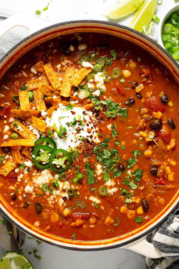 Overhead shot of a large pot of vegan lentil tortilla soup garnished with fresh chopped cilantro