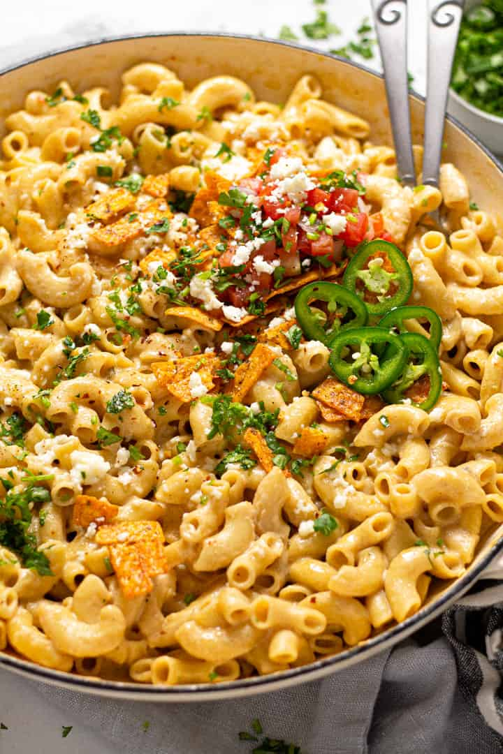 Close up shot of a large pan filled with Mexican mac and cheese garnished with fresh cilantro