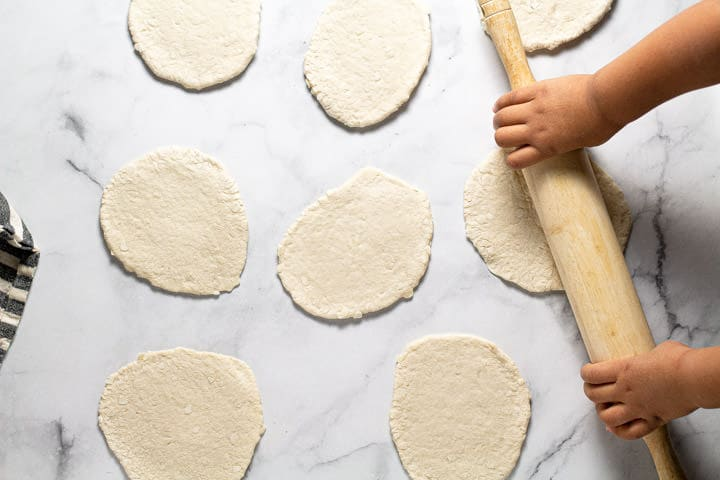 A rolling pin rolling biscuit dough into larger circles